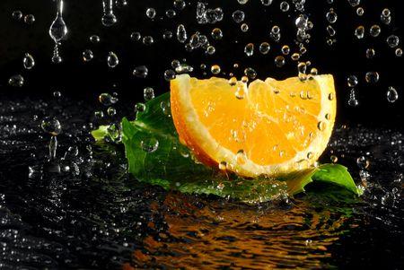 Orangeand leaf placed under heavy tropical rain Stock Photo