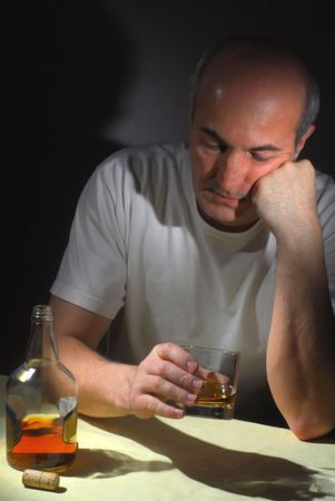 Extreme close-up image of  drunk man holding a glass of whiskey