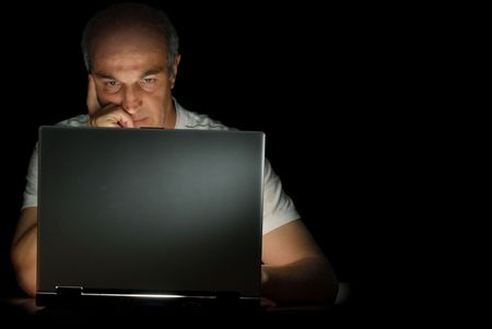 A male businessman working at his computer late at night