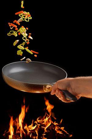Flipping veggies with pan studio isolated on dark background