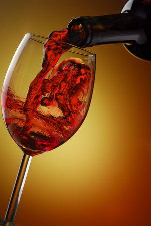 wine pouring: Vino rosso versando in un bicchiere con sfondo astratto