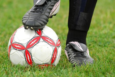 soccer cleats: Close-up image of soccer ball and cleats with grass background Stock Photo