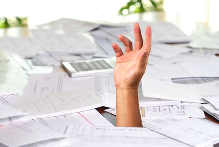 A large amount of bills spread all over the place with hand asking for help Stock Photo - 5938957