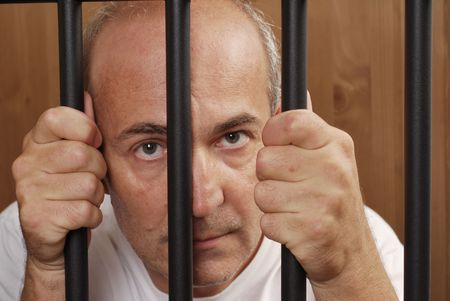 jail: A man in prison holding bars with his hands looking distressed Stock Photo