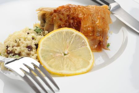 lemon wedge: A plate with chicken, couscous and a lemon wedge. Stock Photo