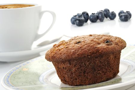 Tasty homemade muffins placed on plate withblueberries and coffee in background photo