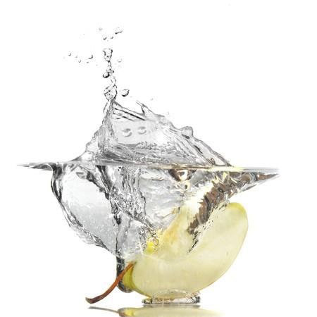 Close-up image of en apple and splash studio isolated on white background photo