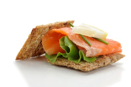 Close-up of smoked salmon served with crackers, lemon and salad photo