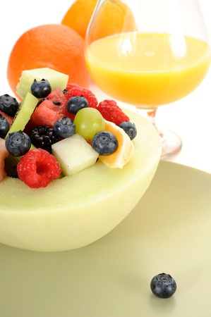 Close-up image of a fruit salad with juice and oranges in background photo