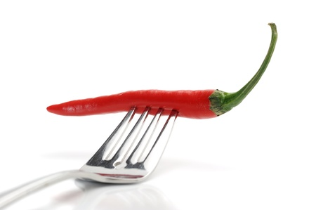 Red hot chilli pepper and fork on white background