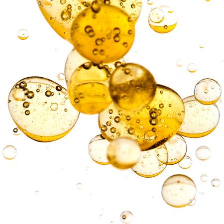drop: Cierre de las burbujas doradas sobre fondo iluminado