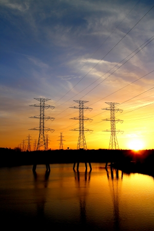 High voltage power line towers on a field with beautiful sunset photo
