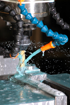 milling machine: Milling machine making part while coolant is spraying