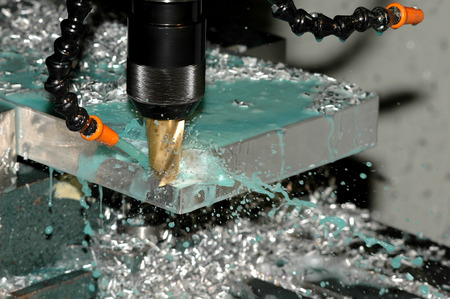 Milling machine is making part while coolant is spraying Stock Photo