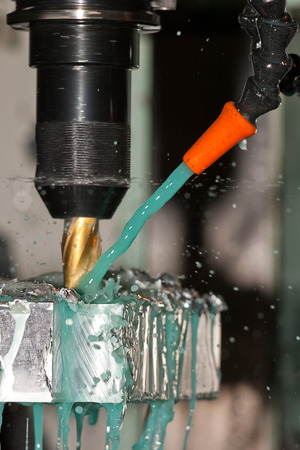 coolant: Milling machine is making part while coolant is spraying Stock Photo