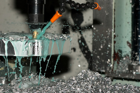 Milling machine making part while coolant is spraying photo
