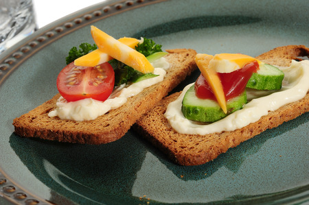 Crackers served on plate with cucumber, tomato and cheese