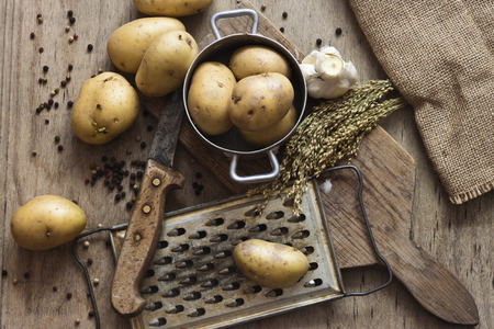 grater: Potatoes, grater, old knife and garlic on a wooden table