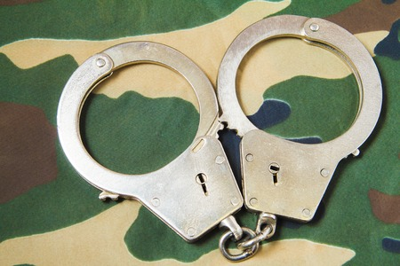 restraints: Police closed shiny handcuffs on camouflage background