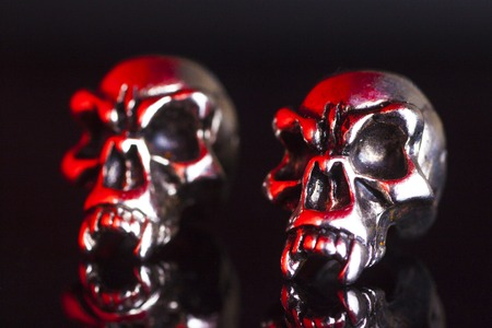 death metal: two metal skull on a black background red tint Stock Photo