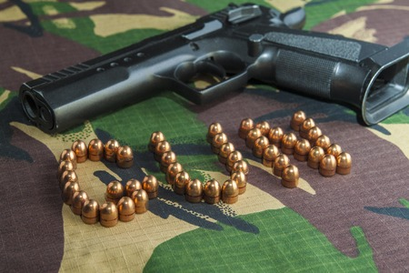 casings: Firearm Pistol Clip And Hand Gun Ammunition on military camouflage background