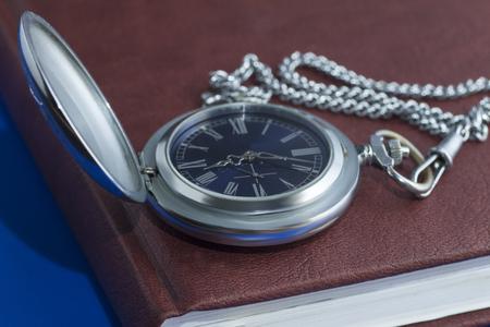 puntualidad: reloj de bolsillo en la página del diario en el fondo azul
