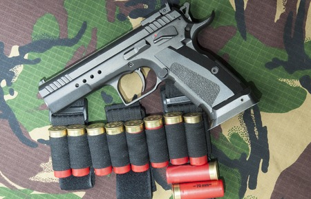 machined: Firearm Pistol Clip And Hand Gun Ammunition on military camouflage background