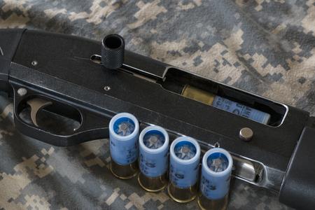 camouflaged: pump shotgun with ammunition on camouflaged background