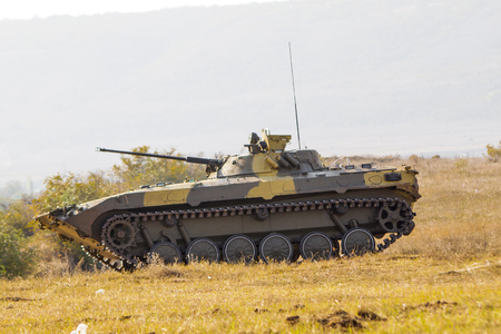military machine in camouflage standing in a field Stock Photo