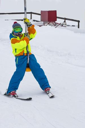 Happy child boy enjoying vacation in winter resort. Sport for family.