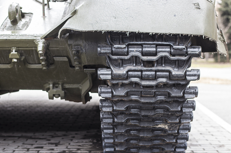 view of the front part of the green caterpillar of the tank standing on the ground with the wheels close-up