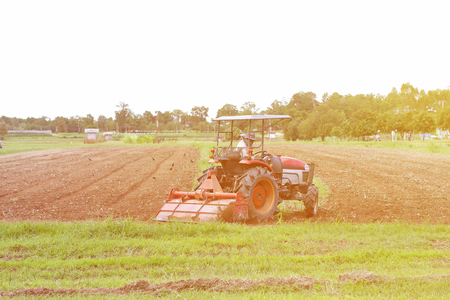 seed bed: Farmer in tractor preparing land with  cultivator effcet soft light blur and nosie