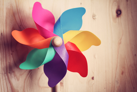 playthings: Colored windmill on on wood background .effect vintage. Stock Photo