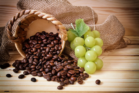 Vintage photo with coffee wood background and Basket and grapes in a sack.use vintage effect style blur and noise .