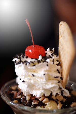 ice cream, whipped cream, cherries on the top.