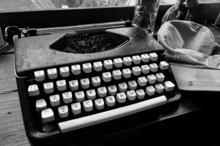 Vintage typewriter style on a wooden table with a hat placed on the table 版權商用圖片