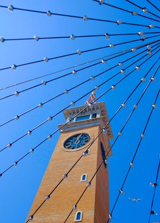 The orange clock tower from the block, the blue sky and the vertical wires look strange.