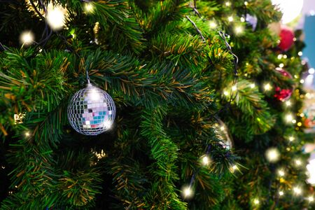 The ball decorated the Christmas tree with beautiful sparkling lights.