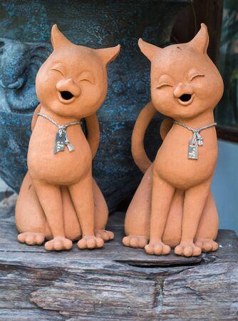 Terracotta cat statue pairs on a cute log Foto de archivo