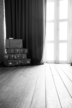 The room has an empty leather bag near the curtains and has light from the glass door in black and white tone.