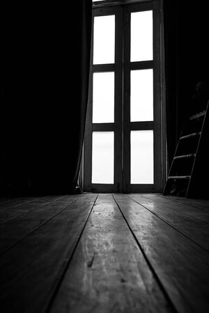 Curtains and light from glass doors, old wooden floors, black and white images, but only yellow tones