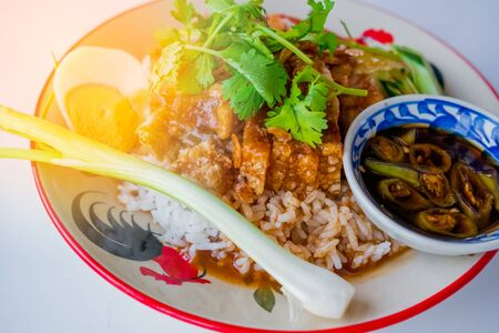 Crispy pork rice topped with a sweet sauce and with onions and cucumbers beside the plate ready to be eaten