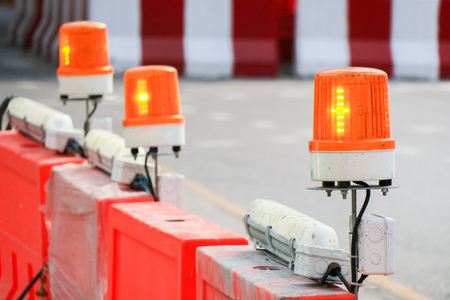 Orange flashing and revolving light on top of fence, Sirens with blurred background , message under construction. Stock Photo
