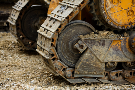 gear handle: big crawler wheel, The Crawler close up , muddy crawler chain detail in earthy ambiance, Well used excavator tracks closeup