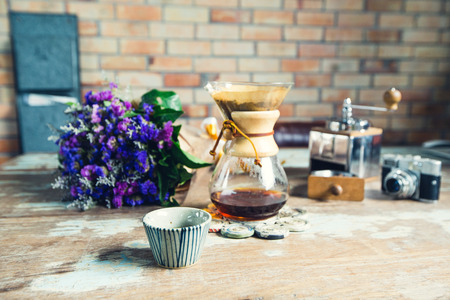 View of ground coffee pouring water on coffee ground with filter, Flower Film Camera and brick wall background, Colour Retro style. Copy space for your text. Thailand
