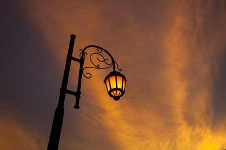 Vintage illuminated street lamps orange light with sunset cloud orange color background Stock Photo