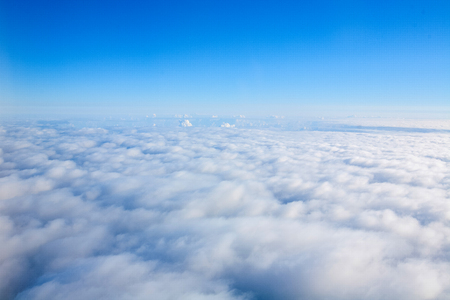 View of Airplane trace over the clouds.Flying in the sky over the clouds. Blue sky background 写真素材