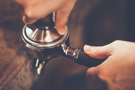 バリスタは、タンパーを使用して挽いたコーヒーを押します。小さなコーヒー ビジネス コンセプト portafilter と手にクローズ アップ。色ビンテージ