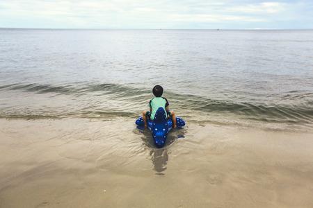 夏の暑い日に屋外でカラフルなインフレータブル リング形状おりますと遊ぶ幸せな少年。子供たちは泳げるようになります。子供の水のおもちゃ。