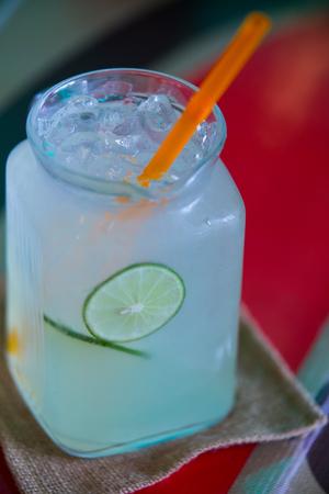 ガラスとオレンジのストローでライムにおいしい冷たいレモン ジュース